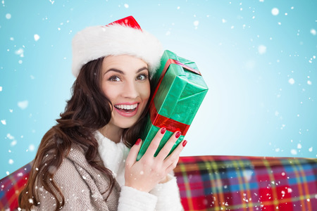 and guessing: Festive brunette holding gift against blue vignette
