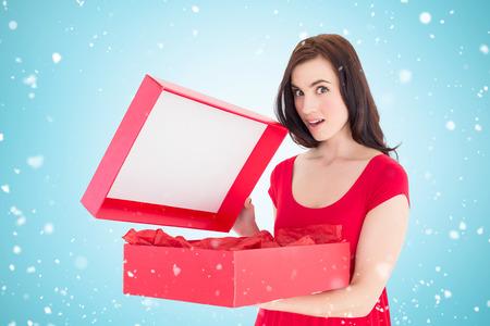opening gift: Surprised brunette in red dress opening gift against blue vignette