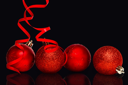 red glittery: Composite image of Four red christmas ball decorations against black
