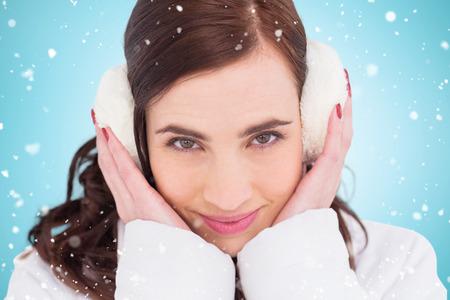 ear muffs: Pretty brunette with ear muffs against blue vignette