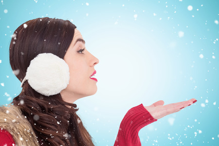 hand out: Brunette in winter clothes with hand out against blue vignette Stock Photo