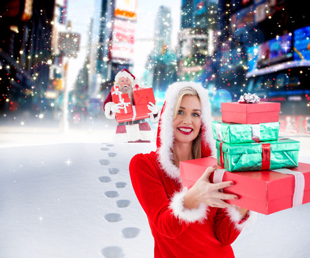 adult footprint: Festive blonde holding pile of gifts against santa delivering gifts in city