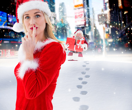 pere noel sexy: Festive blonde keeping a secret against santa delivering gifts in city Banque d'images