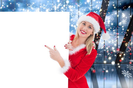 pere noel sexy: Festive blonde showing white card against glittering lights in room