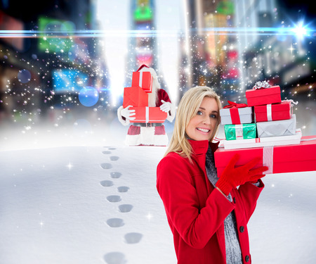 adult footprint: Festive blonde holding many gifts against santa delivering gifts in city Stock Photo