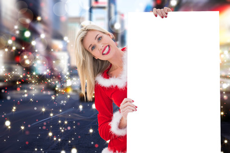 pere noel sexy: Festive blonde showing white card against blurry new york street Banque d'images