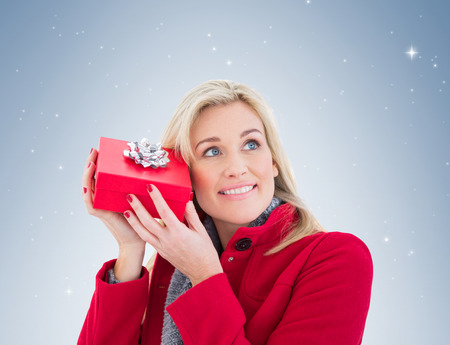 guessing: Festive blonde holding red gift  on vignette background