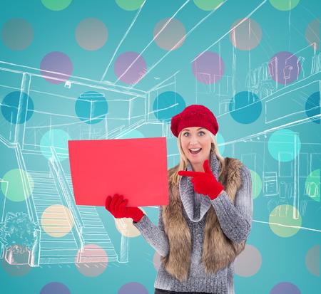 rood teken: Blonde in winter clothes holding red sign against blue vignette Stockfoto