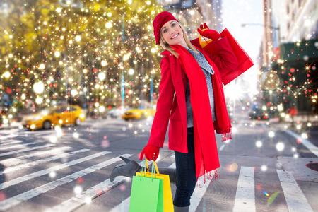 Happy blonde in winter clothes holding shopping bags against blurry new york street
