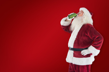 clear away: Father Christmas drinks beer with closed eyes against red background Stock Photo