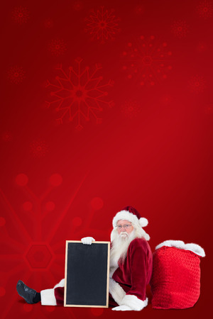 leaned: Santa sits leaned on his bag with a board against red background Stock Photo