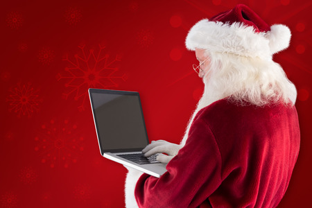 uses: Santa Claus uses a laptop against red background