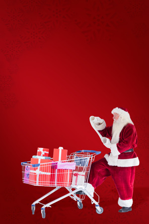 pushes: Santa pushes a shopping cart while reading against red background Stock Photo