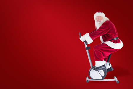 home trainer: Santa uses a home trainer against red background