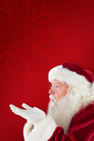 blows: Santa Claus blows something away against red background