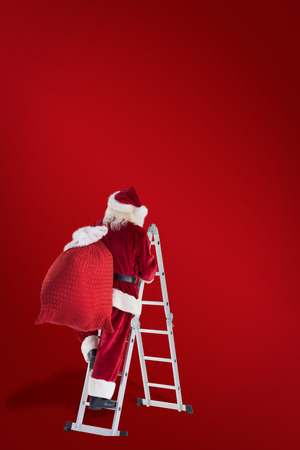 christmas time: Santa steps up a ladder against red background