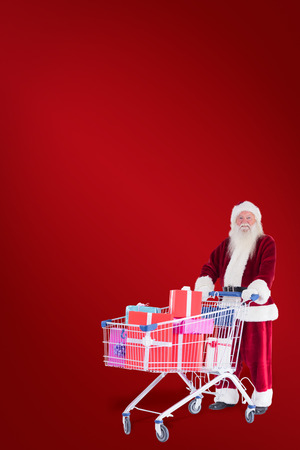 pushes: Santa pushes a shopping cart with presents against red background Stock Photo