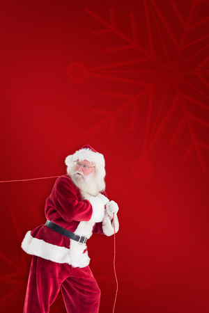 clear away: Santa pulls something with a rope against red background Stock Photo