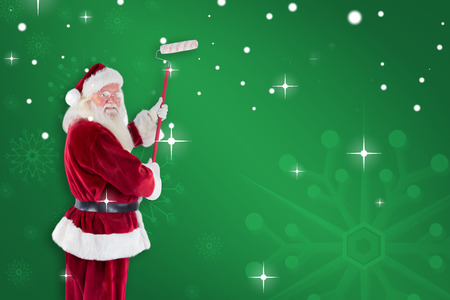 pere noel: Father Christmas paints a wall against green snowflake background Banque d'images