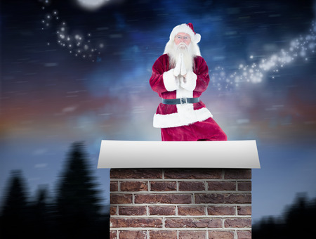 Father Christmas doing some yoga against snow falling on fir tree forest Stock Photo