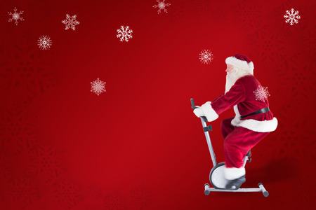 home trainer: Santa uses a home trainer against red snowflake background Stock Photo