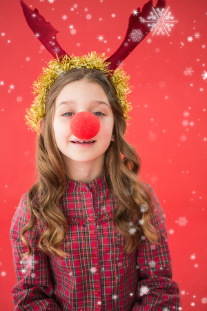 nariz roja: Festive little girl wearing red nose against snow falling