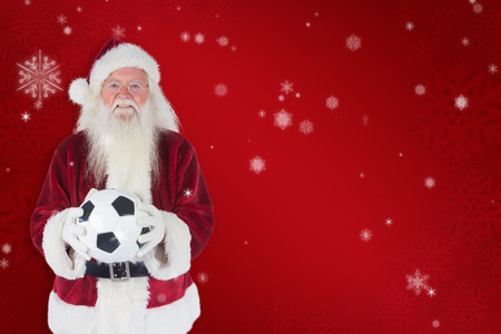 christmas costume: Santa holds a classic football  against red snowflake background Stock Photo