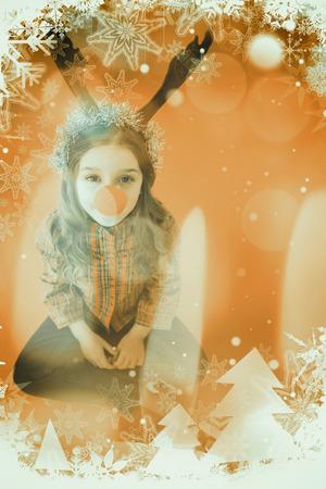 nariz roja: Ni�a festiva que desgasta la nariz roja contra vela encendida contra fondo festivo