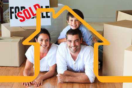 Family in their new house lying on floor with boxes against house outline Stock Photo