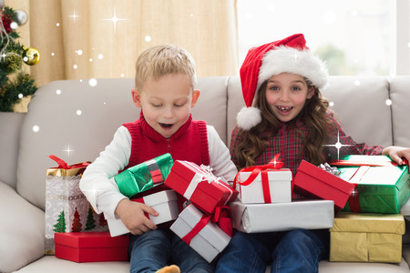 siblings: Festive siblings surrounded by gifts against snow Stock Photo