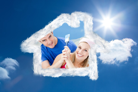 paintrush: Hugging couple having fun while painting a room against bright blue sky with clouds