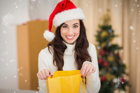 opening gift: Festive brunette opening gift bag  against snow falling Stock Photo