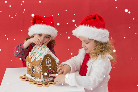 gingerbread house: Festive little girls making a gingerbread house against snow