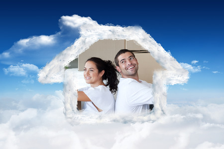 mortage: Radiant couple with unpacking boxes moving to a new house against bright blue sky with clouds