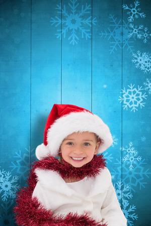 wearing santa hat: Cute little girl wearing santa hat and tinsel against snowflake pattern on blue planks