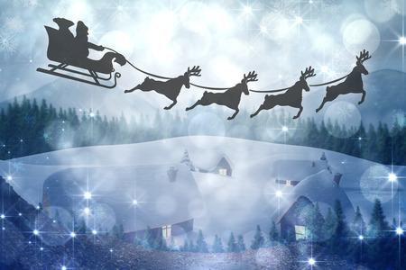 santas village: Silhouette of santa claus and reindeer against cute village in the snow