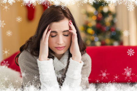 pounding head: Brunette getting a headache on christmas day against fir tree forest and snowflakes Stock Photo
