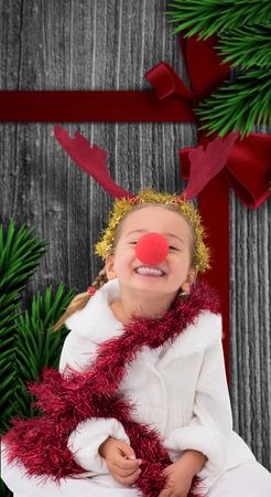 nariz roja: Ni�a linda que desgasta la nariz roja y oropel contra la madera con arco festivo Foto de archivo