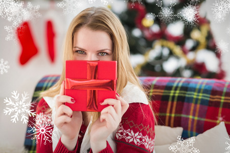 woman hiding: Young woman hiding behind a gift against snowflakes