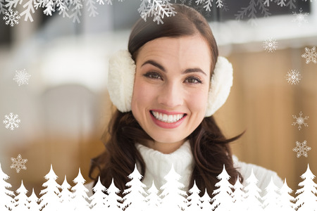ear muffs: Beauty brunette with ear muffs smiling at camera against fir tree forest and snowflakes