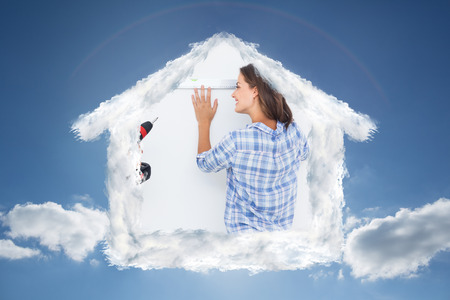 cloudy home: Cheerful man and his wife doing home improvements together against cloudy sky with sunshine Stock Photo