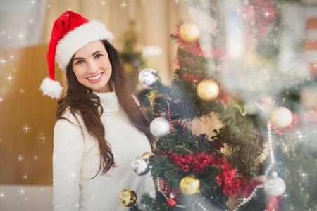 decorating christmas tree: Smiling brunette decorating a christmas tree against snow Stock Photo