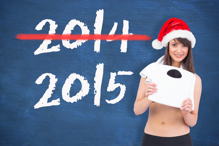 weighing scales: Festive fit brunette holding a weighing scales against blue chalkboard