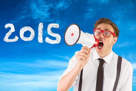 businessman using a megaphone: Geeky businessman shouting through megaphone against blue sky