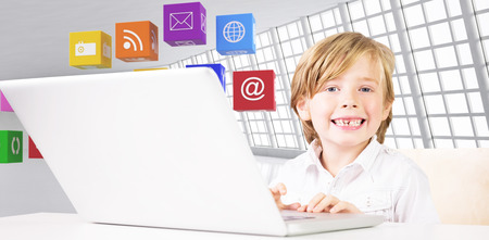 against abstract: Cute boy using laptop against abstract room Stock Photo