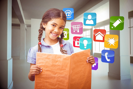 Cute pupil smiling at camera during class presentation against computing application icons