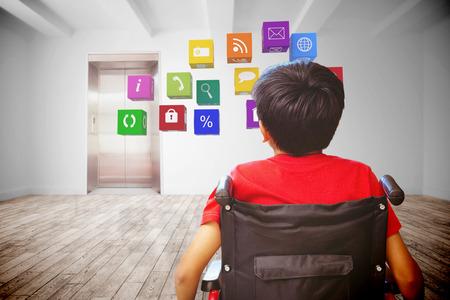 niños discapacitados: Vista trasera de un niño sentado en la silla de ruedas contra el cuarto con ascensor Foto de archivo