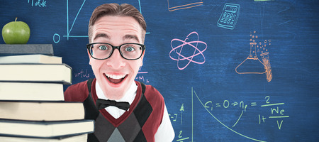 cheesy grin: Smiling geeky hipster looking at camera against blue chalkboard Stock Photo