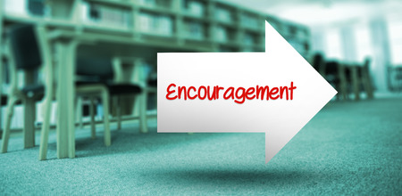 volumes: The word encouragement and arrow against volumes of books on bookshelf in library
