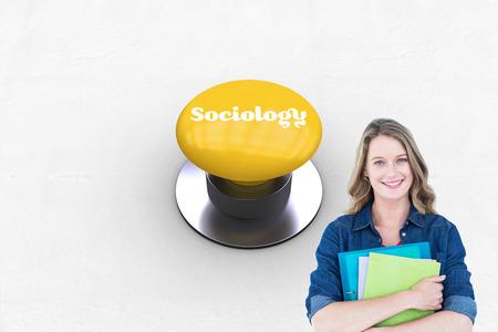 sociologia: La palabra sociología y estudiante sonriente sosteniendo portátil y el archivo contra pulsador amarillo